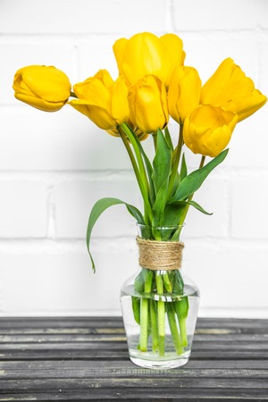 transparent vase with yellow tulips,holiday concept