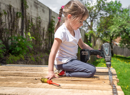 little girl outdoors repairing with screwdriver and wrench in hand, tightening bolts on a wooden background,closeup, concept of repair