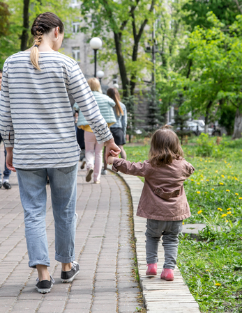a little girl goes hand in hand with mom in the Park ,the concept of children