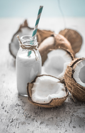 coconuts on a wooden background with a jar of coconut milk closeup ,concept fresh coconuts
