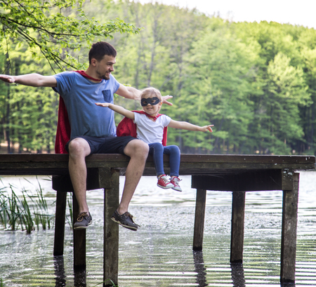 Happy loving family, father and daughter playing a super hero in the open air near the river on the wooden pier,the concept of a super hero and a childs dreams,fathers Day Stock Photo
