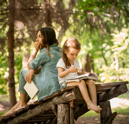 mladistvý: Young mother and daughter read a book in the park on a wooden bridge, the concept of a happy family life and family relations