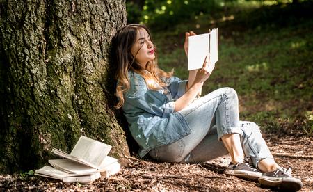 poblíž: Girl reading a book near a tree in the park