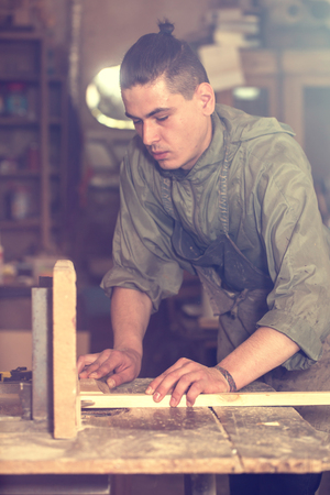 mitre: a man works on the machine with the wooden product manufacturing