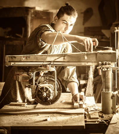 a man works on the machine with the wooden product manufacturing