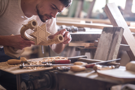 hand carved: male carpenter working with a wood product, hand tools, close up Stock Photo