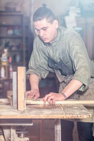 mitre: a man works on the machine with the wooden product Stock Photo