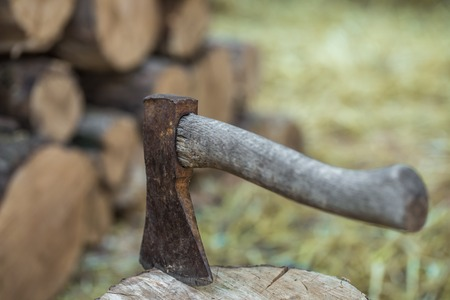 A deck of stacked logs and an axe in a log,the concept of drilling wood