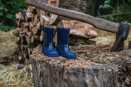 childrens rubber boots stand on the beam ,the concept of camping and recreation Stock Photo