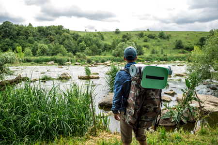 a young guy with a Hiking backpack on his shoulders,the concept of travel and summer vacation