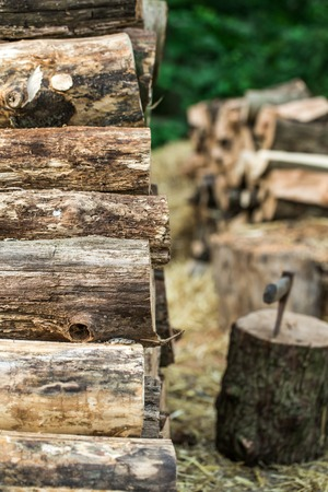 A deck of stacked logs and an axe in a log,the concept of drilling wood Banque d'images