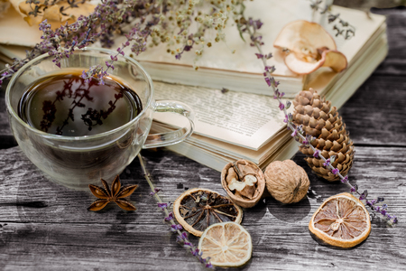 Beautiful transparent Cup of tea with autumn leaves and dried lemon on a wooden pallet on nature background