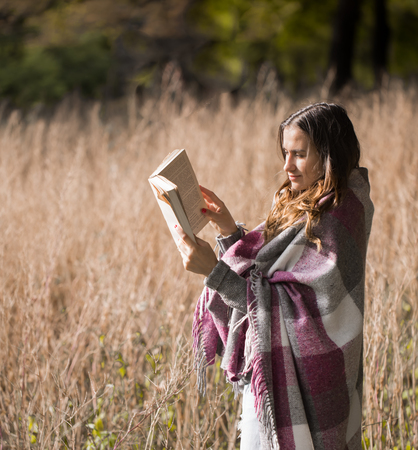 young beautiful sweet girl on the field reading a book, the concept of rest and reading