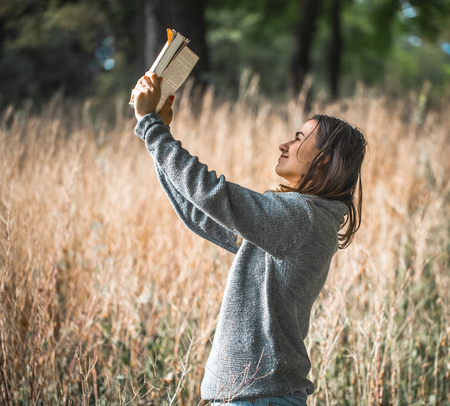 young girl on a field reading a book Stock Photo