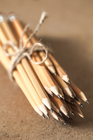 a stack of graphite pencils tied with rope on wooden background ,closeup Stock Photo