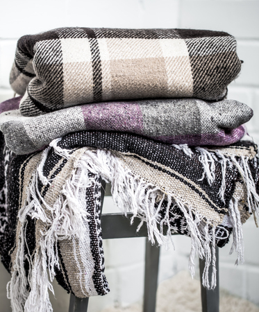 warm cozy blankets stacked on a chair,the concept of warmth and comfort