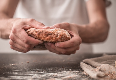bakery products: the preparation of bread, fresh bread in hands closeup on old wooden background, concept for baking