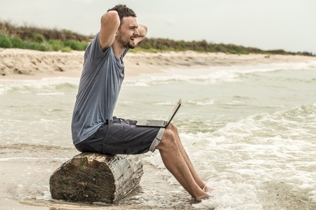 the man working at a computer in nature, work on the beach