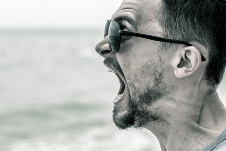 portrait of a man, the cry of a man in sunglasses closeup black and white photo