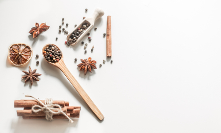A variety of Oriental spices on a wooden spoon isolated on white background, concept of spicy food and spices