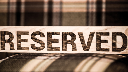wooden sign saying reserved,close-up ,background ,concept hotels and restaurants