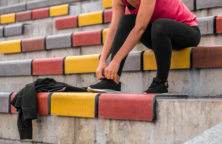 athletic wear: Sports fitness girl tying laces on sneakers, the concept of fitness and sports healthy lifestyle