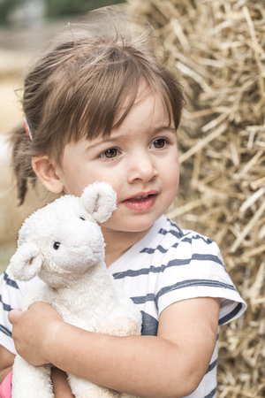 little cute girl plays with a toy sheep ,the concept of childhood and children Stock Photo
