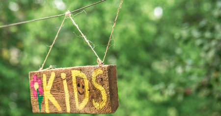 the kids inscription on a wooden sign hanging on a rope, the concept of children and childrens holiday