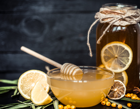 composition lemon tea in a transparent glass with a handle and a plate with honey ,the concept of hot drinks and health Stock Photo