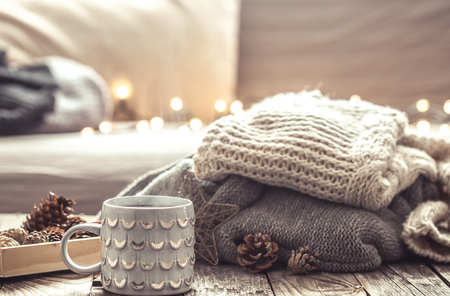 ホーム インテリア リビング ルームの静物の詳細。美しい紅茶カップと木製の背景に靴。居心地の良い秋冬コンセプト