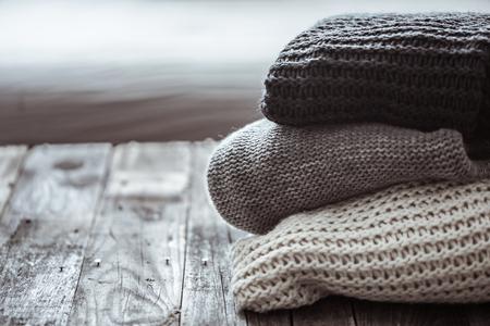 나무 배경에 아늑한 니트 스웨터의 스택. 가을 - 겨울 개념 스톡 콘텐츠