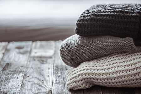 stack of cozy knitted sweaters on wooden background. Autumn-winter concept