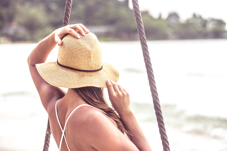 beautiful girl in a hat sitting on rocked back on the beach of Thailand