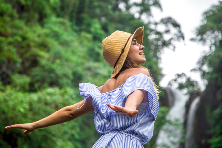 Beautiful girl in hat looking at the waterfall, the concept of leisure and travel Stock Photo