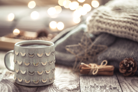Details of still life in the home interior living room. Beautiful tea Cup and shoes on wooden background . Cosy autumn-winter concept Stock Photo