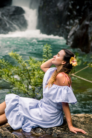 Beautiful girl in a dress and a Hibiscus flower in her hair sitting by the waterfall, the concept of leisure and travel Stock Photo