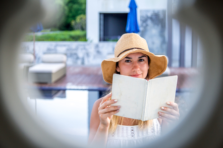 A young girl in a hat reading a book on holiday ,the concept of reading and relaxing , shooting through the lumen