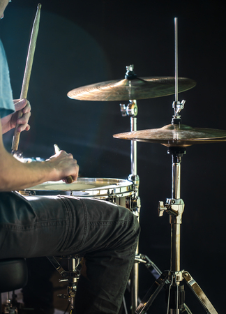 man plays the drum, close-up, flash of light, a beautiful light in the background with copy space