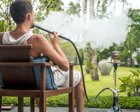 man smoking a hookah on vacation background lifestyle concept