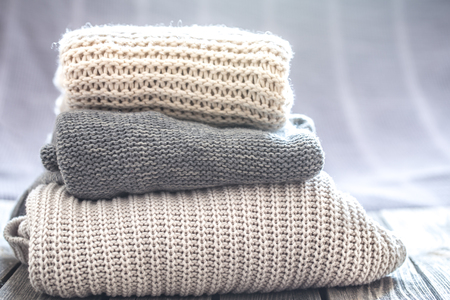 beautiful knitted clothes, neatly folded, close-up, handmade knitted sweaters