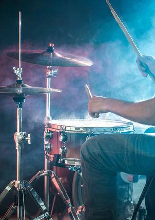 男はドラムを演奏し、クローズアップ、光のフラッシュ、コピースペースを持つ背景に美しい光