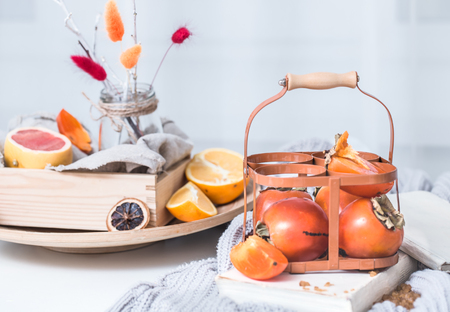 Still life fresh persimmon in a basket on a serving table preparation for breakfast concept of holding