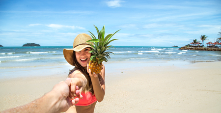 Beautiful girl in swimsuit and pineapple walks on the beach holding the hand of the guy, a romantic walk