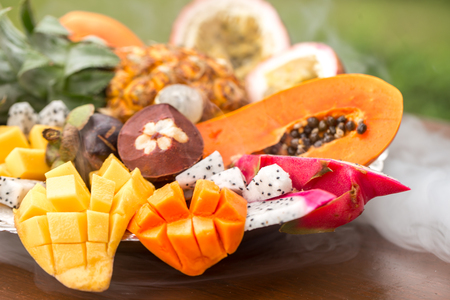 Exotic fruits in smoke from a hookah close-up on a tray