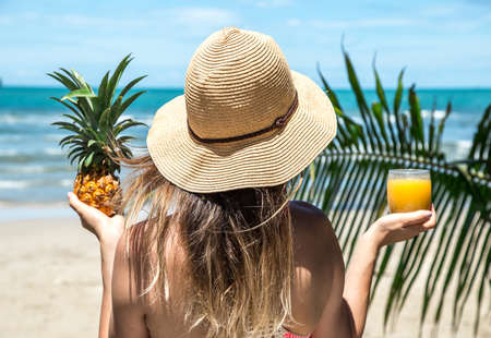 girl in swimsuit and hat drinks juice near tropical on beach concept of rest