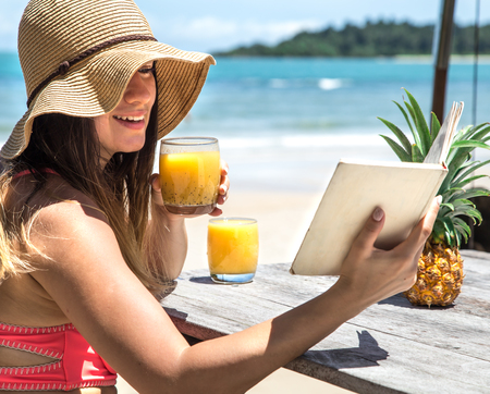 girl in a hat near a tropical beach sitting at a wooden table drinking juice and reading a book end of a rest Stock Photo