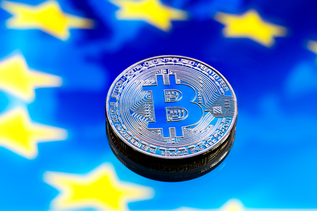 coins Bitcoin, against the backdrop of Europe and the European flag, the concept of virtual money, close-up. Conceptual image of digital crypto currency.