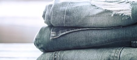 Folded stack of jeans on a wooden background, concept of stylish clothes