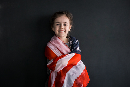 Little cute girl with the American flag on a dark background, the concept of Americas Day and patriotism