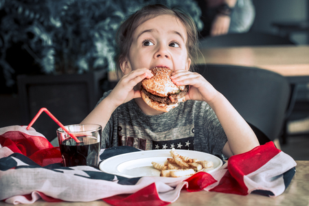 little girl in T-shirt with American flag in cafe eating a burger and drinking a drink, concept of America Day and American food